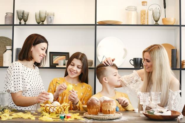 부활절 달걀을 그리는 어머니와 아이들.