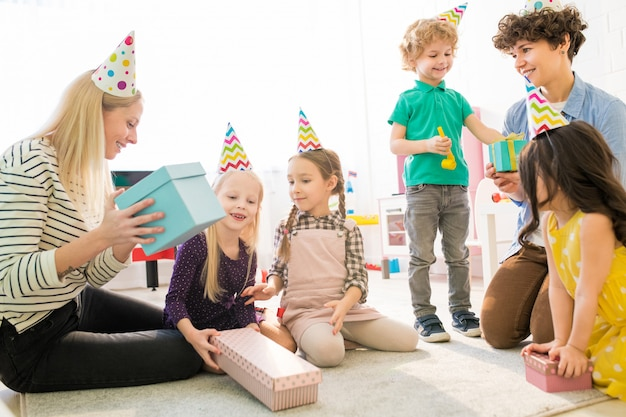Mothers and children guessing what is inside of gift box
