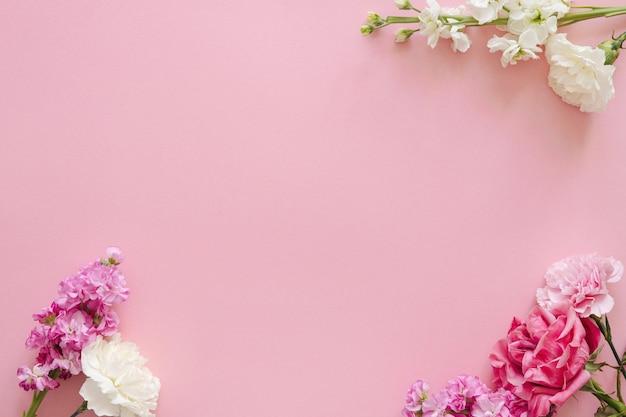 母の日と休日のデザインコンセプト-母の日、結婚式、バレンタインデーのピンクの背景バナーにカーネーションとバラの上面図とモックアップビューのコピースペース