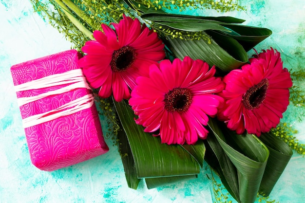 Mothers day background or greeting card bouquet red flowers of gerbera and a present