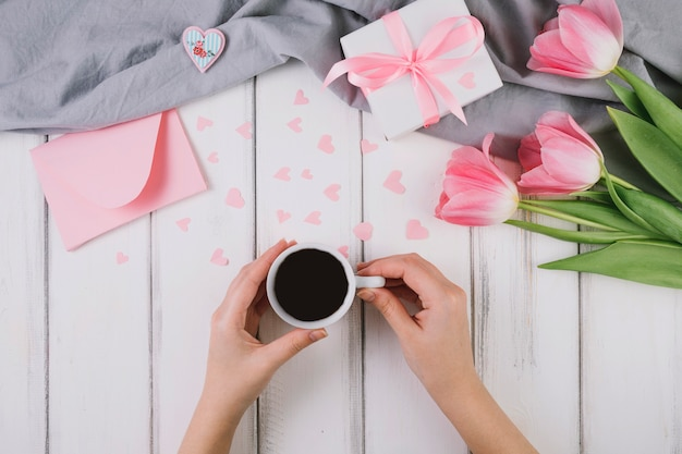 Mothers day background with hands holding coffee cup