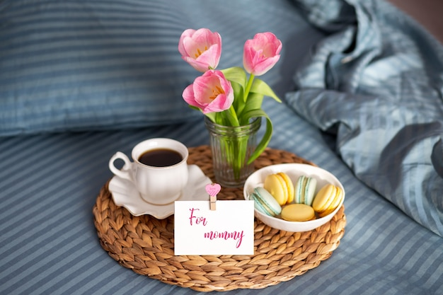 母の日。ママのためのベッドでの朝食。地図と一杯のコーヒーをベッドで朝食します。一杯のコーヒーとマカロン。おはようございます。お母さんのためのグリーティングカード。チューリップunmade pastel with breakfast