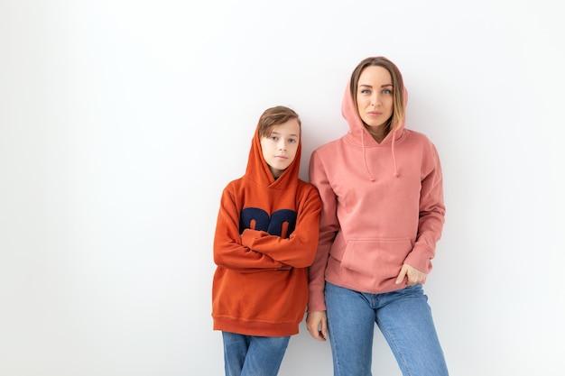母の日、子供と家族の概念-コピースペースで白い壁に彼のお母さんを抱き締める10代の少年