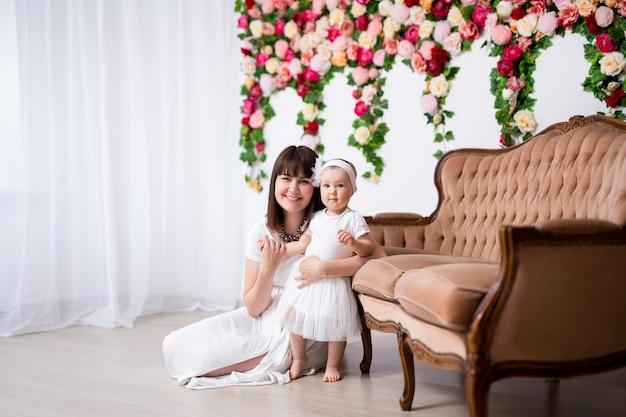 Концепция дня матери счастливая мать и ее маленькая дочь над стеной цветов