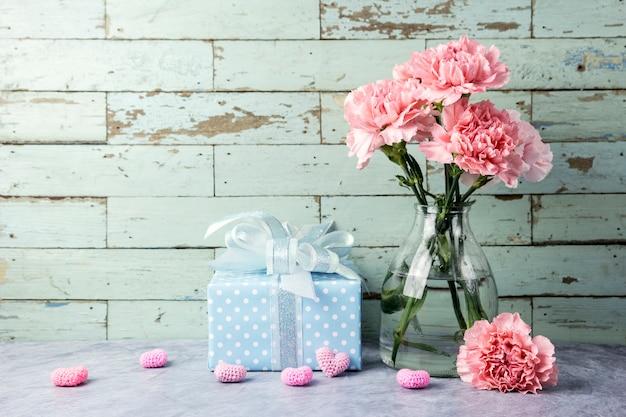 명확한 병 및 선물 상자와 마음에 분홍색 카네이션 꽃의 어머니의 날 개념