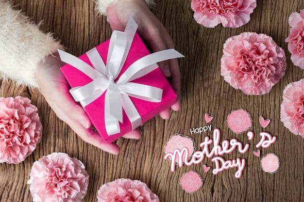 분홍색 선물 상자를 들고 젊은 여자 손의 어머니의 날 개념