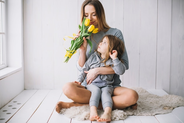Mothers day concept with mother and daughter smelling flowers