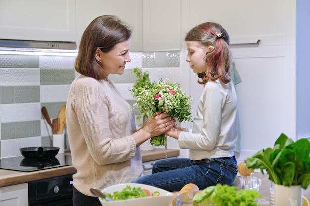 День матери, дочка ребенка дарит маме букет весенних цветов