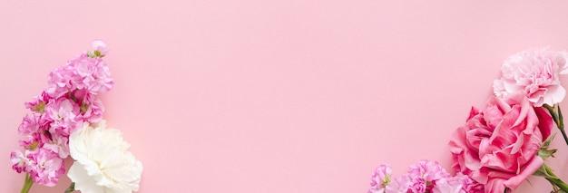 母の日のデザインコンセプト-母の日、結婚式、バレンタインデーのピンクの背景バナーにカーネーションとバラの上面図とモックアップビューのコピースペース