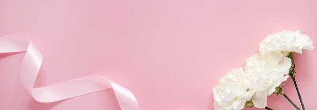 母の日のデザインコンセプト-母の日、結婚式、バレンタインデーのピンクの背景バナーにカーネーションの上面図とモックアップ上面図のコピースペース
