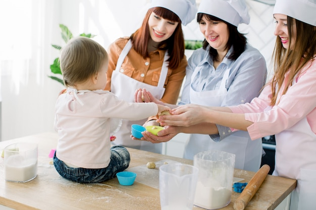 Mothers day, family, cooking and people concept - little cute baby girl and her mom, aunt and grandmother making and decorating cupcakes at home kitchen
