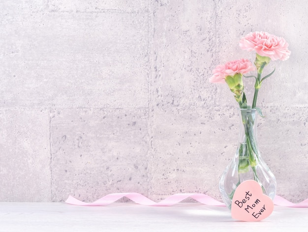 Mothers day handmade giftbox surprise wishes photography - beautiful blooming carnations with pink ribbon box isolated on gray wallpaper design, close up, copy space