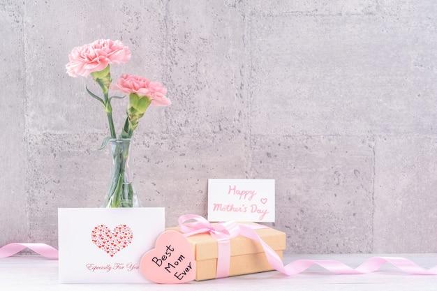 母の日の手作りギフトボックスの驚きの願いの写真撮影-灰色の壁紙デザイン、クローズアップ、コピースペースで分離されたピンクのリボンボックスと美しい咲くカーネーション