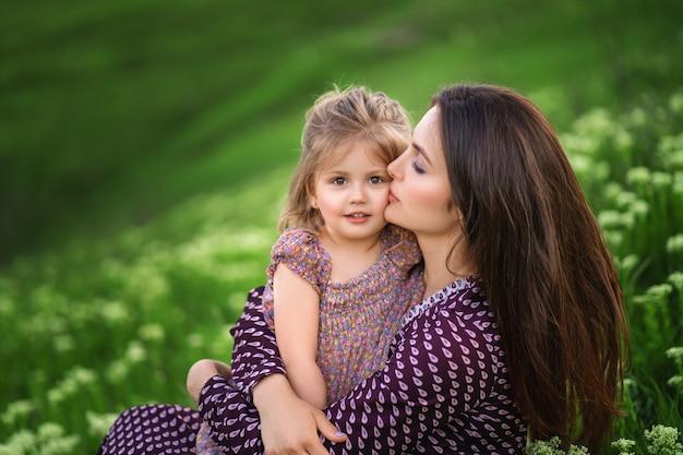 母の日のお母さんは小さな娘にキスをします