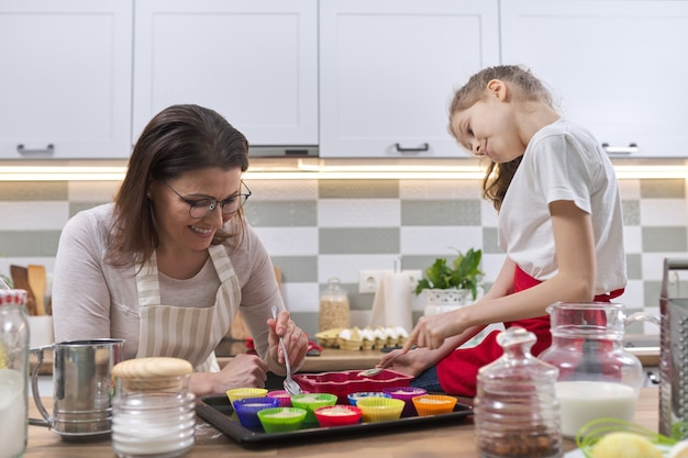 Mothers day, mother and daughter child 9, 10 years old preparing cupcakes together at home in kitchen, woman teaching child cooking