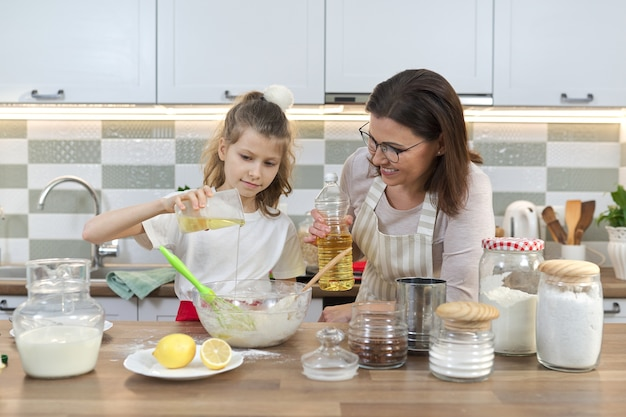 Mothers day, mother and daughter child together at home kitchen preparing cookies