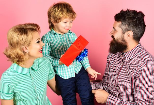 母の日または誕生日。休日に母親を祝福する父親と息子。幸せな家族。
