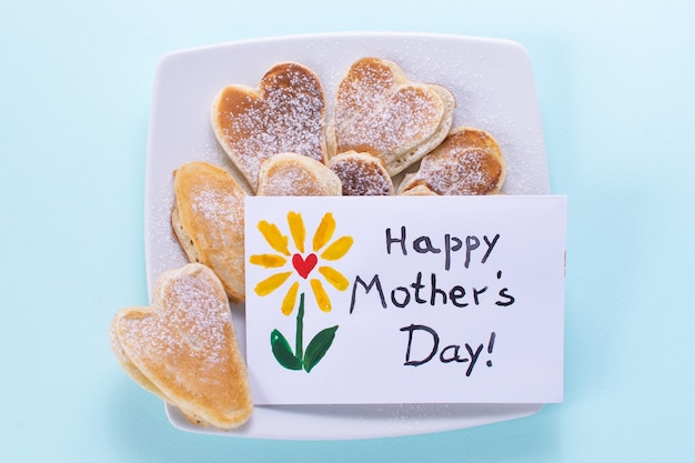 Mothers day postcard with heart shaped pancakes breakfast on blue background