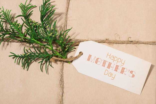 母の日。木製の背景に色の花で紙にタグを付けます。上面図。モックアップ