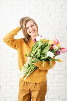 어머니의 날, 여성의 날 개념. 봄 방학. 튤립 꽃다발을 들고 행복 한 젊은 여자