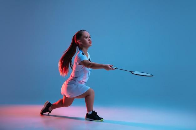 운동. 네온 불빛에 파란색 배경에 고립 된 배드민턴에서 연습 하는 아름 다운 난쟁이 여자. 포용적인 사람들의 라이프스타일, 다양성과 평등. 스포츠, 활동 및 움직임. 광고에 대 한 copyspace입니다.