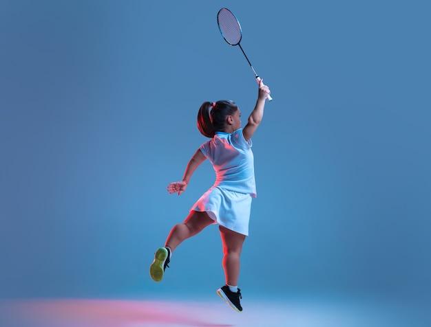 운동. 네온 불빛에서 파란색으로 격리된 배드민턴에서 연습하는 아름다운 작은 여자