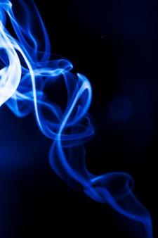 黒の背景に青い煙を動かします。