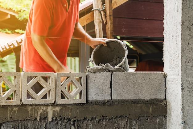 自宅で建設のためのビルドを作業しているモーションブラー煉瓦工の男 Premium写真