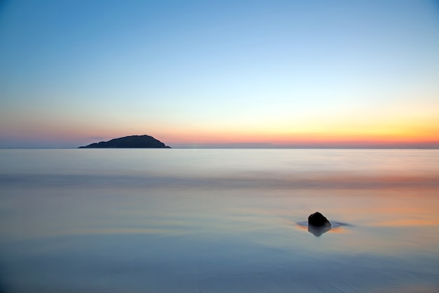 鮮やかな夕暮れの夕焼け空の下で海の動きのぼかし