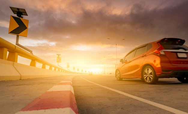 Motion blur of red car driving on curve concrete road with a traffic sign. road trip on summer vacation. car drive on the street. summer travel by car. solar panel energy on yellow curve traffic sign