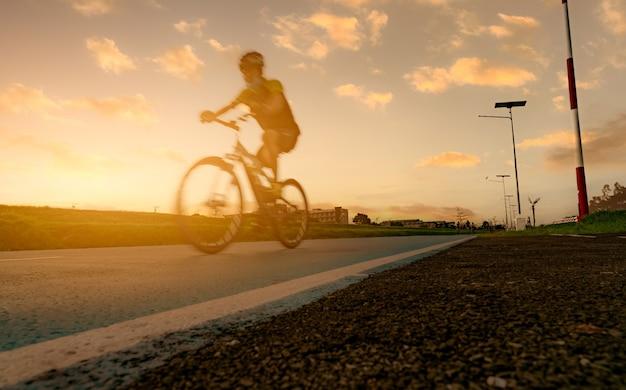 모션 블러 스포츠 남자는 일몰 하늘과 저녁에 도로에서 속도 동작으로 자전거를 타고. 건강하고 행복한 삶을 위한 여름 야외 운동. 자전거 차선에서 산악 자전거를 타는 자전거 타는 사람.