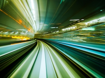 Motion blur train moving in city rail tunnel. High speed vehicle background abstract.