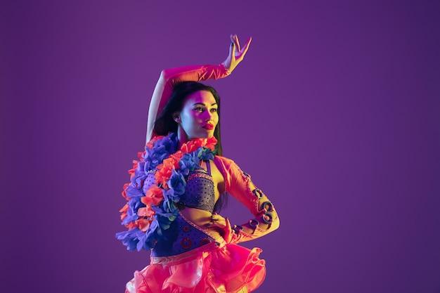모션 댄스. 네온 불빛에 보라색 벽에 하와이 갈색 머리 모델. 웃 고 재미 전통 옷을 입고 아름 다운 여자. 밝은 휴일, 축하 색상, 축제.