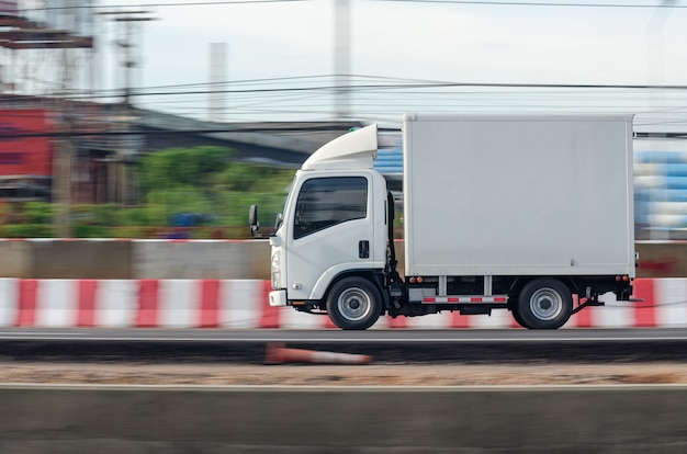 도로 주행 운송을 위한 작은 흰색 트럭의 모션 이미지 프리미엄 사진