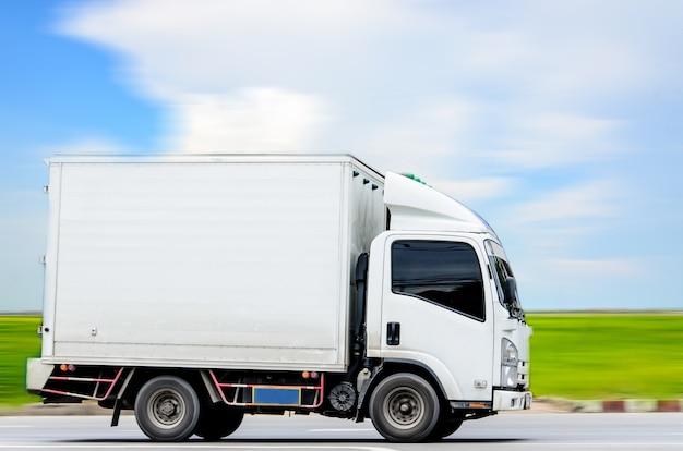 푸른 하늘 배경에 푸른 잔디와 흰 구름이 있는 흰색 트럭의 모션 이미지