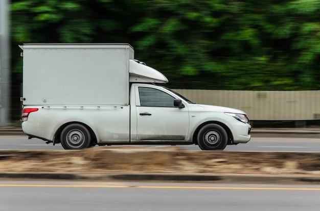 모션 이미지, 물류 사업을 위해 도로를 달리는 작은 흰색 트럭.