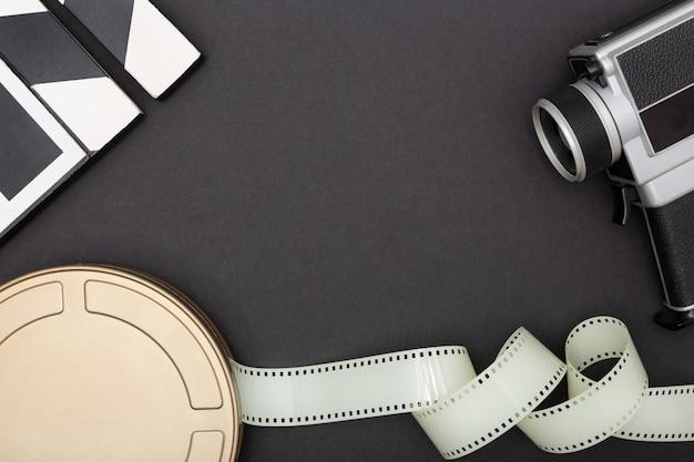 映画フィルム缶、フィルムカメラ、黒の背景のフィルムストリップ。映画やテレビの背景。トップビューコピースペース