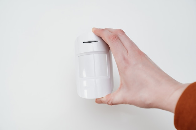 Motion sensor in hand on white background. device that tracks the movement of objects. it is used to automate operation of electrical appliances, surveillance video cameras, alarms and security system