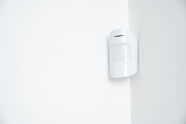 Motion sensor oin the white corner. device that tracks the movement of objects. it is used to automate the operation of electrical appliances, surveillance video cameras, alarms and security system