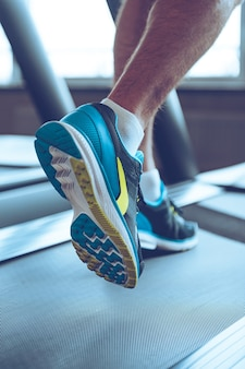 Motion and strength. close-up part of man in sports shoes running on treadmill at gym