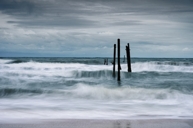 Motion of wave hitting decay wooden bridge on the beach in stormy weather