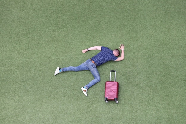 Motionless man lies on green lawn with suitcase