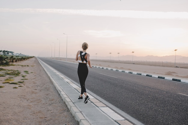 晴れた朝に道を走って戻ってからやる気のある驚くべき女性。トレーニング、トレーニング、本当の感情、健康的なライフスタイル、勤勉、強いスポーツウーマン、熱帯の国。