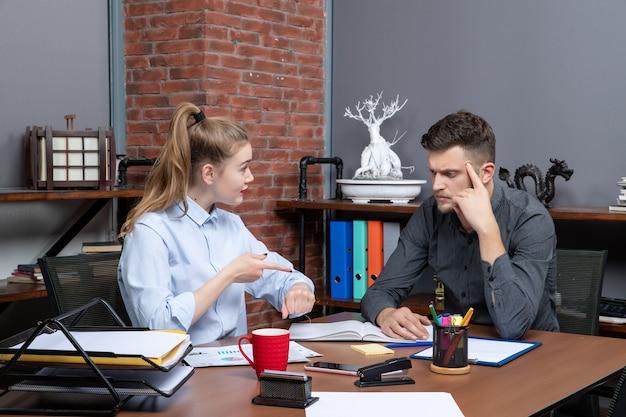 사무실 환경의 회의실 테이블에 앉아 있는 동기 부여되고 바쁜 관리 팀