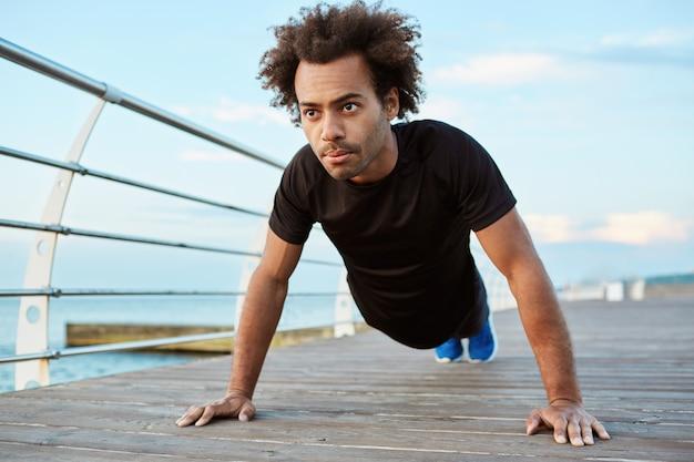 Мотивированный и сконцентрированный афроамериканский спортсмен с густыми волосами в черной спортивной форме стоит в позе доски на деревянной платформе.