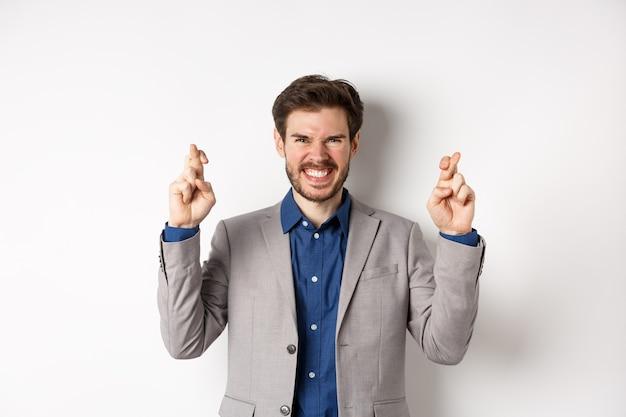 Мотивированный и взволнованный бизнесмен улыбается позитивно, выглядит обнадеживающим и скрещивает пальцы на удачу, загадывает желание, ждет объявления, белый фон.