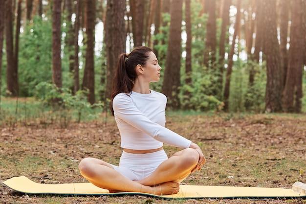 白いレギンスとトップを着た、やる気のある運動のポジティブな女性、ヨガの練習、蓮のポーズで座り、後ろを振り向く