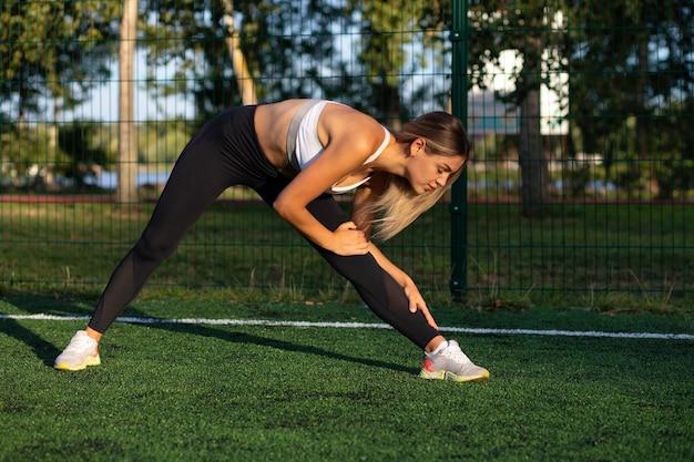 やる気のある金髪のアスリート女性は、サッカー場で屋外トレーニングをする前にウォームアップします。コピースペース