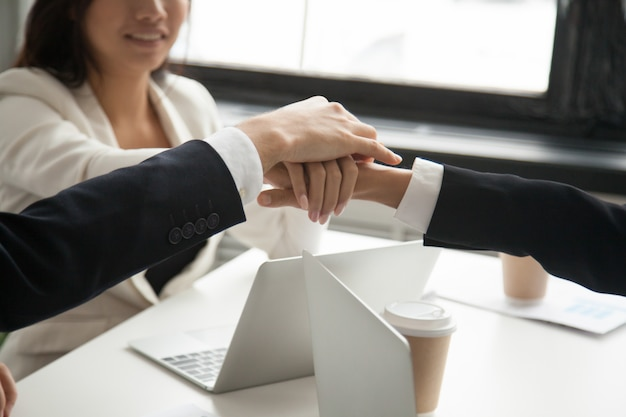Motivated business people put hands together, loyalty engagement concept, closeup