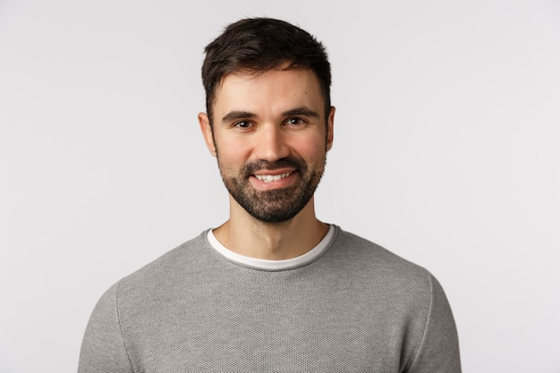 Motivated cheerful and glad, pleasant caucasian adult bearded man in grey sweater, smiling with delighted expression, looking excited and satisfied, nod agreement, give approval